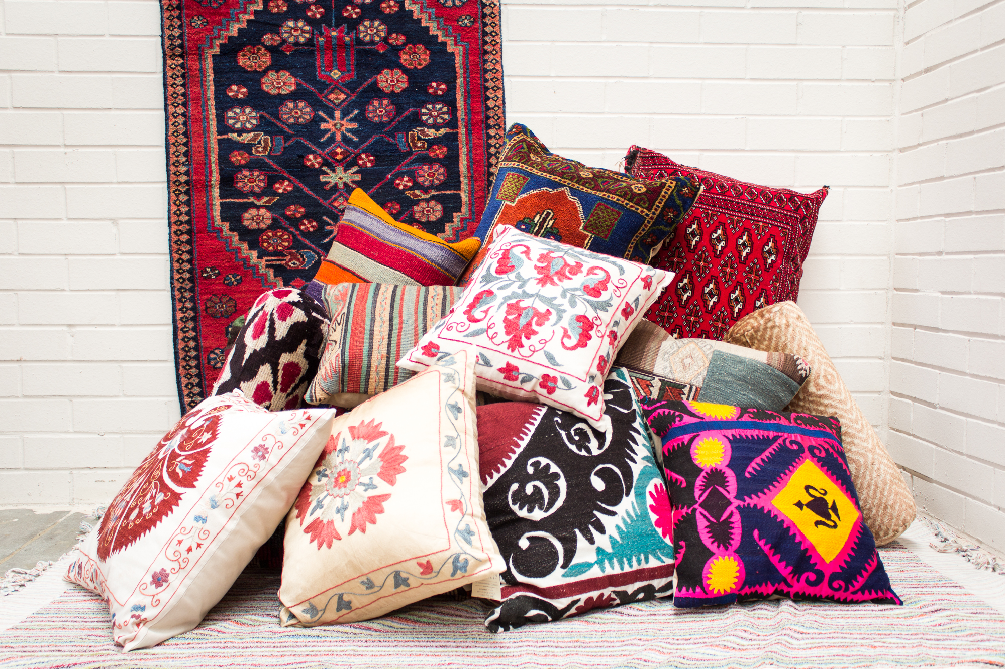 An assortion of Cushion, rug fragments, kilims and susani cushions with a turkish rug in the background